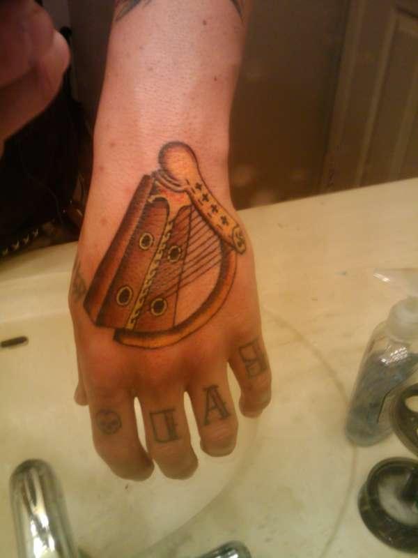 Harp on hand tattoo