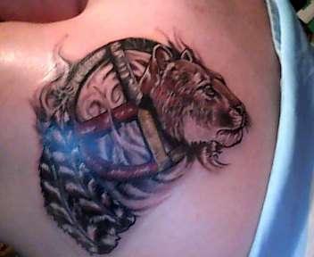 Cougar, medicine wheel, and turkey feathers tattoo