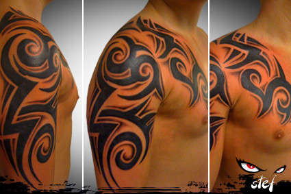 ad9da295462b3 Tribal with shades on chest to arm tattoo