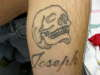 Skull with Biological brothers name underneath tattoo