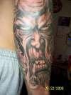 demon eating man tattoo
